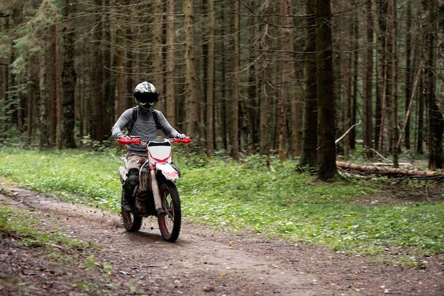 Man in een helm op een motorfiets rijdt op een onverharde weg in het bos