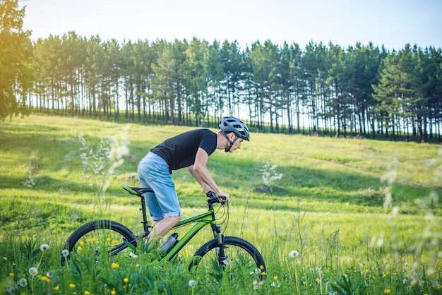 Man in een helm rijden op een groene mountainbike in het bos tussen de bomen. actieve en gezonde levensstijl