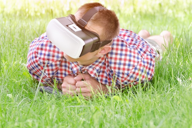 Man in een helm van virtual reality ligt op een groen gras