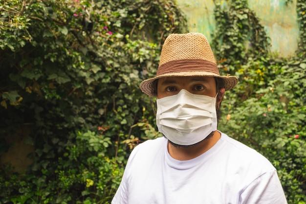 Man in een hoed en een wit overhemd met een gezichtsmasker ter bescherming tegen stof en coronavirus