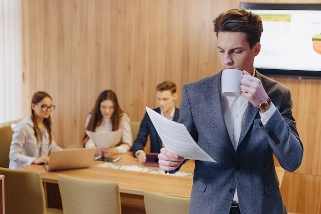 Man in een jas en een shirt met een kopje koffie in zijn hand staat en leest documenten