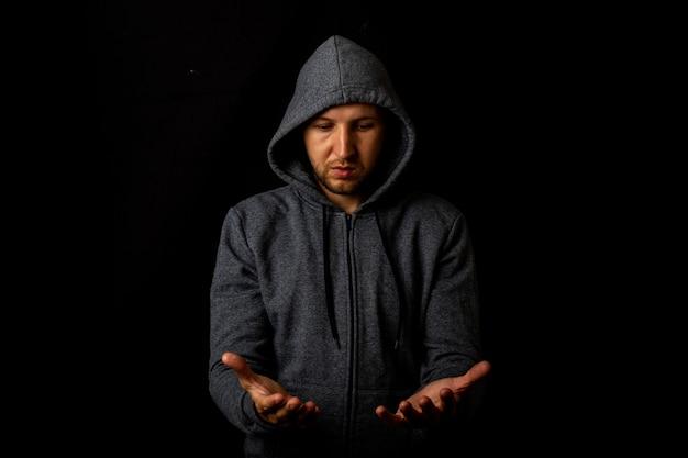 Man in een kap heeft iets in zijn handen op een donkere achtergrond.