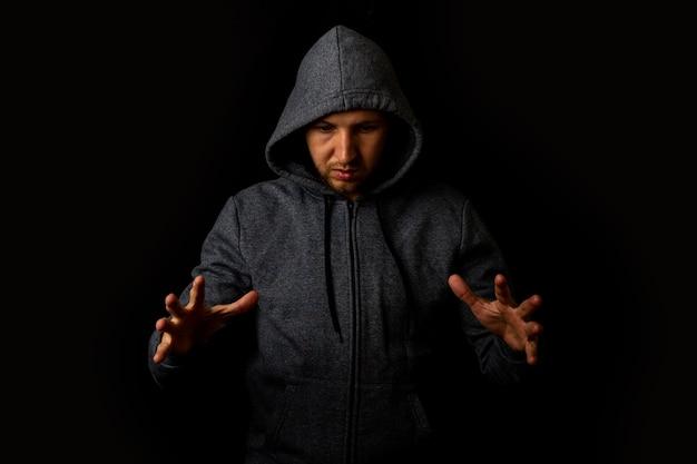 Man in een kap houdt zijn handen op iets op een donkere achtergrond.