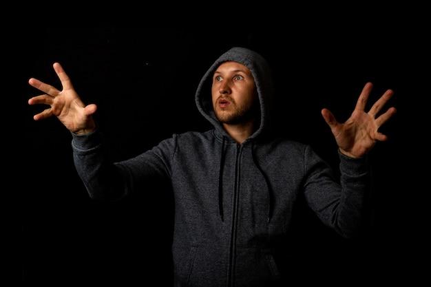 Man in een kap raakt iets op een donkere achtergrond aan.