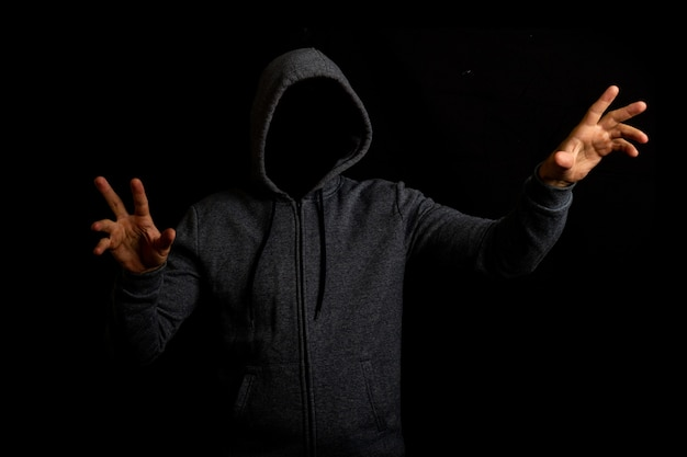 Man in een kap raakt iets op een donkere achtergrond.