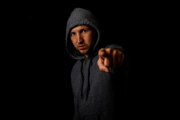 Man in een kap wijst met zijn vinger tegen een donkere achtergrond.