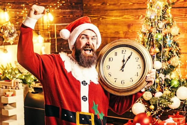Man in een kerstman hoed met een klok