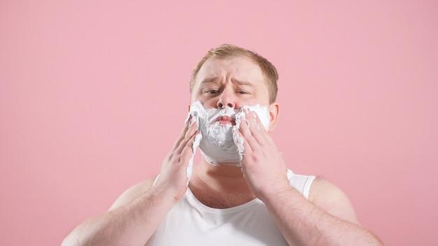Man in een lichaam met scheerschuim op zijn wangen, een man te scheren, geïsoleerde foto op een roze achtergrond