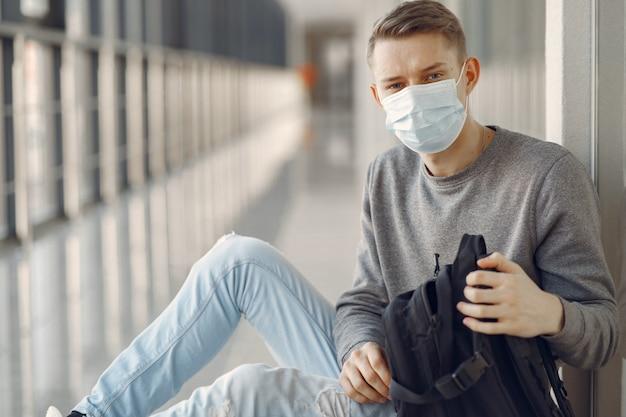 Man in een masker zitten in de hal van het ziekenhuis