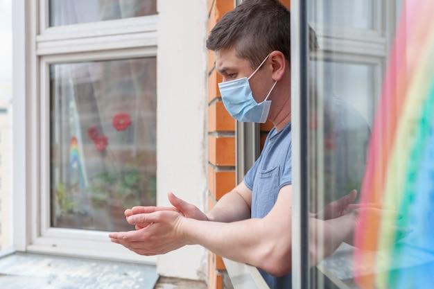 Man in een medisch masker applaudisseert medisch personeel vanaf zijn balkon. er wordt een regenboog op het raam getekend.