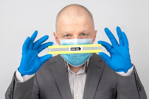 Man in een medisch masker en beschermende handschoenen houdt een bordje met de inscriptie sos info. virus quarantaine