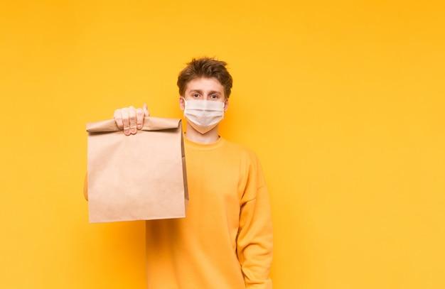 Man in een medisch masker en met een papieren zak poseert op een geel en biedt voedsel uit de bevalling. coronapandemie.