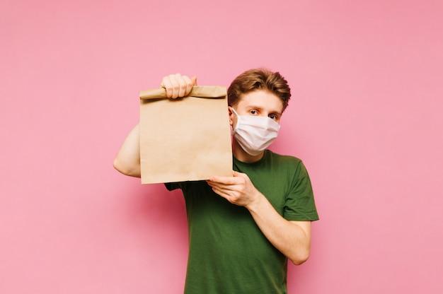 Man in een medisch masker en met een papieren zak vormt op een roze. coronapandemie. quarantaine. covid19.