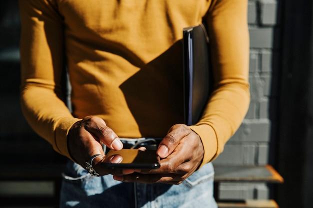 Man in een mosterdgele top met lange mouwen en een zwarte map-aktetas die een telefoon gebruikt