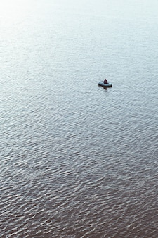 Man in een opblaasbare boot met een hengel in de zee