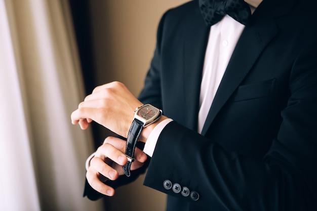 Man in een pak draagt een horloge. een man in een zwart pak. man kijkt naar de tijd. man in een pak. jonge kerel draagt horloges.