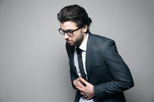 Man in een pak en bril. buikpijn op grijze muur