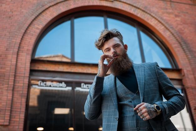 Man in een pak en met een sigaret boven een bakstenen gebouw