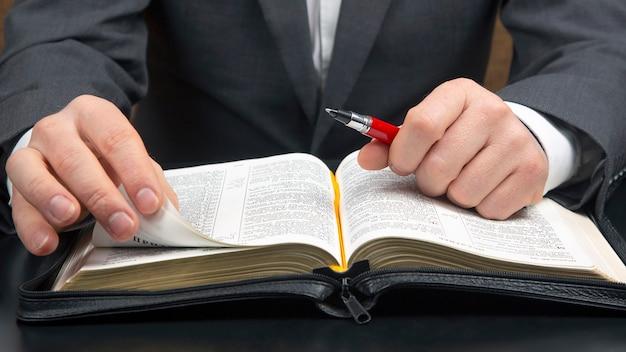 Man in een pak leest de close-up van de heilige bijbel. de studie van religie en christendom