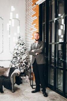 Man in een pak vormt in de buurt van de kerstboom
