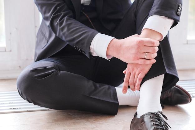 Man in een pak zittend op de vloer
