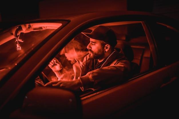 Man in een pet rijdende auto die 's nachts rookt in een garage verlicht met een rood licht, sportwagen