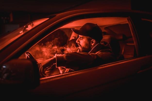 Man in een pet rijdende auto die 's nachts rookt in een garage verlicht met een rood licht Premium Foto