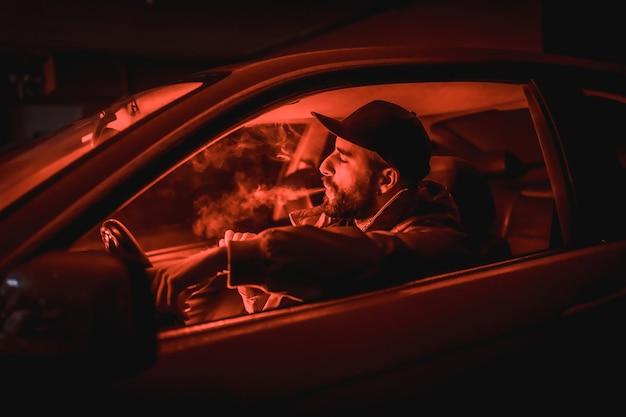 Man in een pet rijdende auto die 's nachts rookt in een garage verlicht met een rood licht