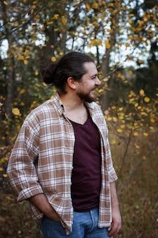 Man in een plaid shirt glimlachend op een herfstwandeling