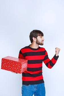 Man in een rood gestreept shirt met een rode geschenkdoos en een teken van plezier.