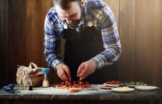 Man in een schort die een pizza bereidt, het deeg kneedt en ingrediënten doet