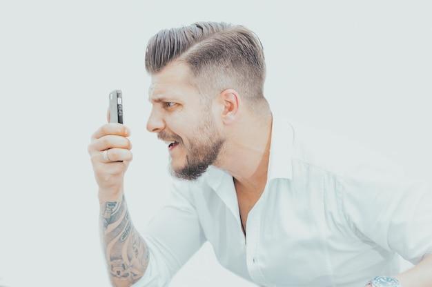 Man in een shirt kijkt verbaasd naar het scherm van de smartphone. concept van mislukte weddenschappen op games, fans, hippodroom. gemengde media
