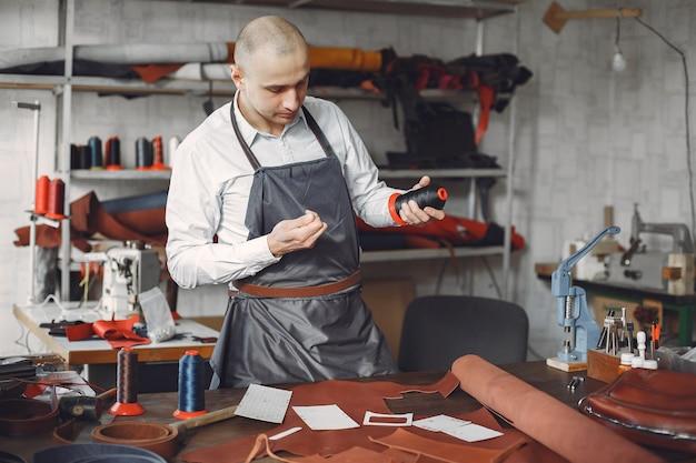 Man in een studio maakt lederwaren