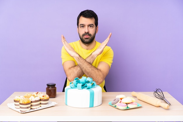 Man in een tafel met een grote cake die geen gebaar maakt