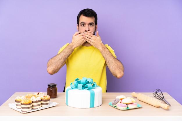 Man in een tafel met een grote cake die mond bedekt met handen