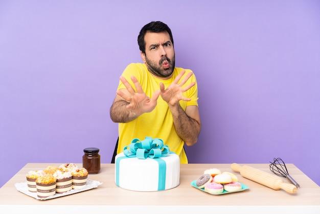 Man in een tafel met een grote cake nerveuze handen naar voren strekken