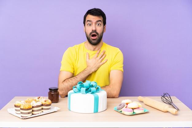 Man in een tafel met een grote cake verrast en geschokt terwijl hij naar rechts kijkt