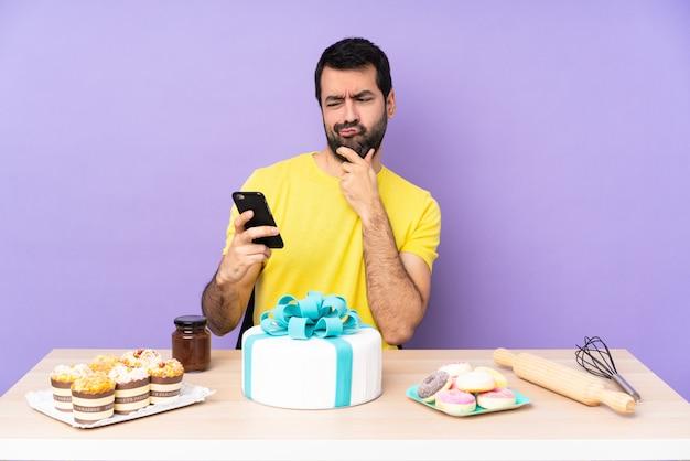 Man in een tafel met een grote taart die denkt en een bericht stuurt