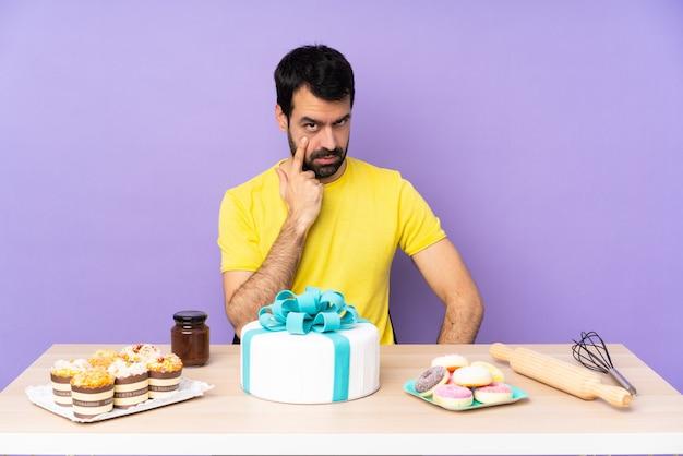 Man in een tafel met een grote taart die iets laat zien