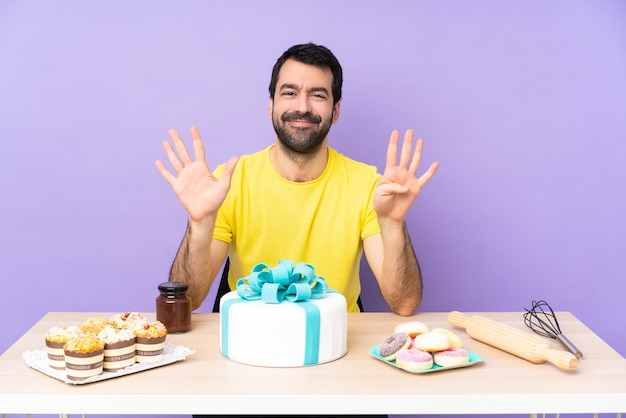 Man in een tafel met een grote taart die negen telt met vingers