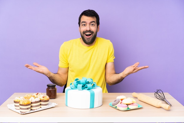 Man in een tafel met een grote taart met een geschokte gezichtsuitdrukking