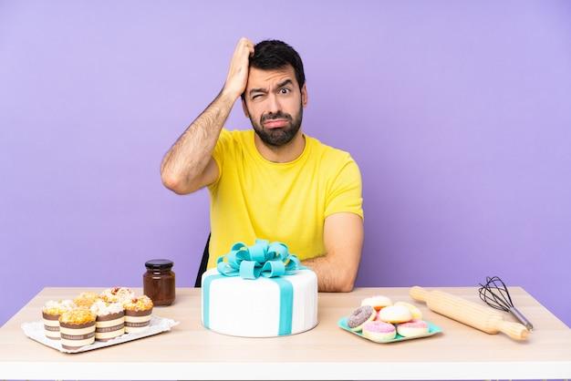 Man in een tafel met een grote taart met een uitdrukking van frustratie en niet begrijpen