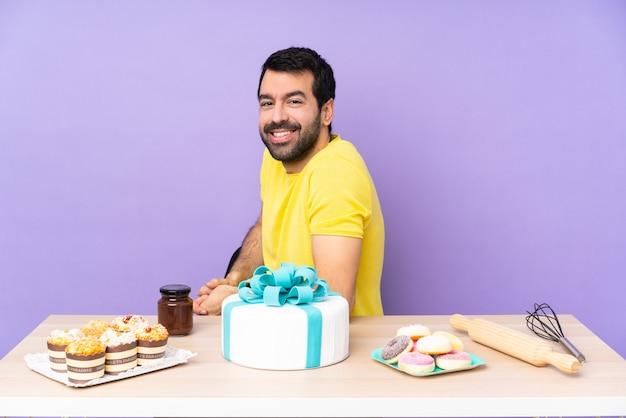 Man in een tafel met een grote taart met gekruiste armen en vooruit kijkend