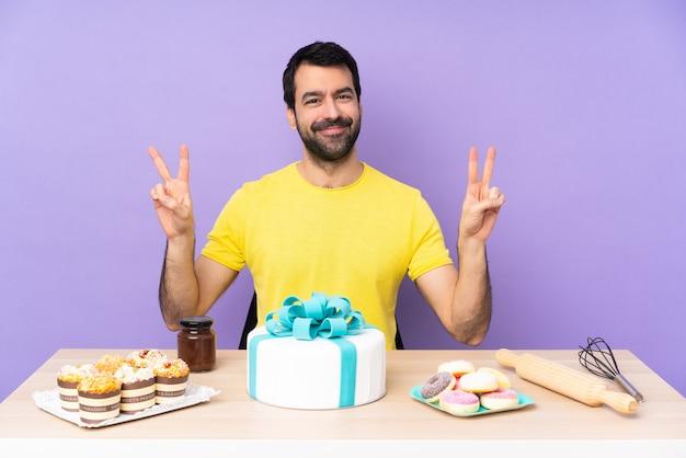 Man in een tafel met een grote taart met overwinningsteken met beide handen