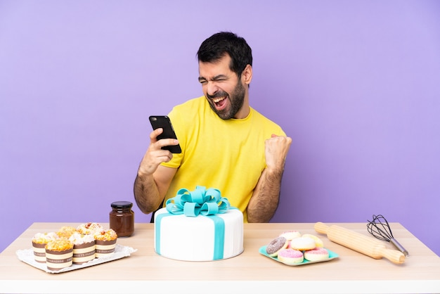 Man in een tafel met een grote taart met telefoon in overwinningspositie