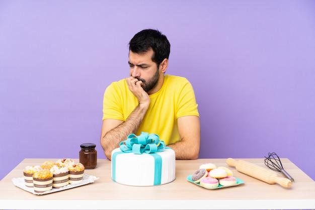 Man in een tafel met een grote taart twijfels