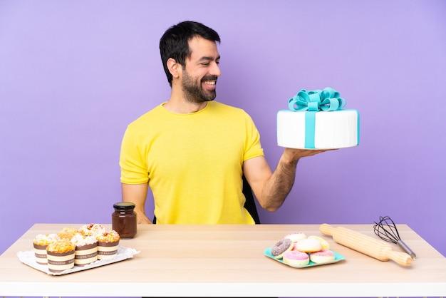 Man in een tafel met een grote taart
