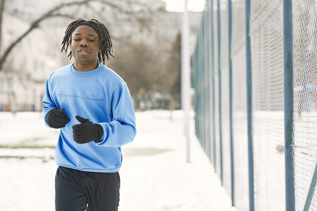 Man in een winterpark. afrikaanse man traint buiten. man rennen.