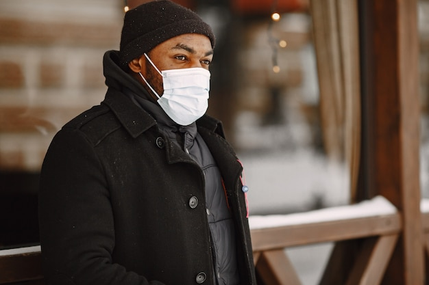 Man in een winterstad. man in een zwarte jas. man in een medisch masker.