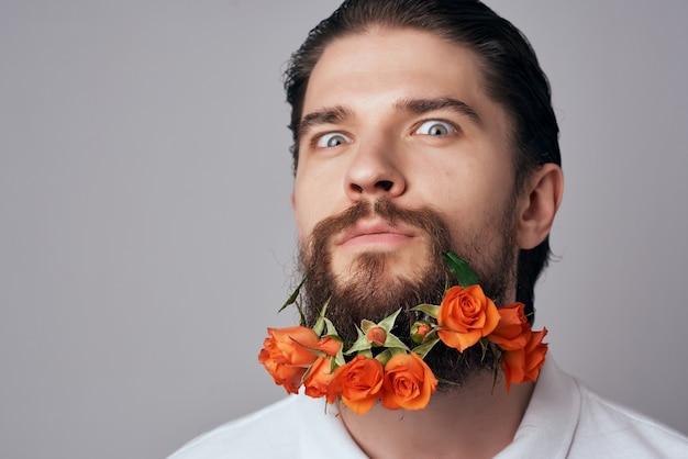 Man in een wit overhemd bloemen in een baard aantrekkelijk uiterlijk sieraden